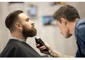 一名年轻男子在理发店梳理胡须_1281019