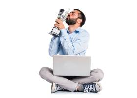 一名手持笔记本电脑的男子手持奖杯_1184613
