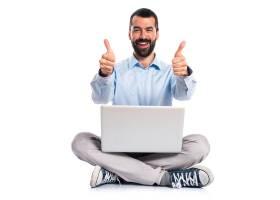一名手持笔记本电脑的男子竖起大拇指_1184578
