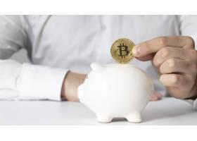 一名男子在存钱罐中插入比特币_11621143