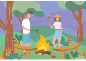 柴火中的男人和女人带着香肠和棍子_4945129