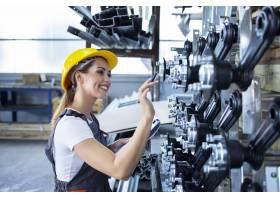身着工作服戴着安全帽的女工业员工在工厂_11034435