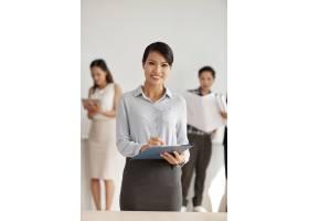 身着时髦服装的亚洲女子在工作室里拿着剪贴_5577069