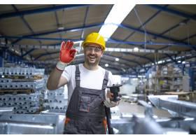 身穿防护装备的工厂工人在生产大厅竖起大拇_11034215