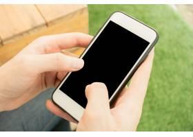 近距离用手触摸手机黑屏自然背景模糊的户_1284976
