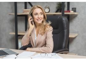 金发碧眼的年轻女商人坐在办公室的椅子上打_3717314