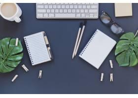 键盘旁的文具和带叶子的桌子上的咖啡杯_5421250