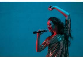 霓虹灯下隔绝在蓝色录音室墙上的女歌手肖像_13058304