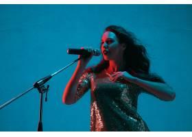 霓虹灯下隔绝在蓝色录音室墙上的女歌手肖像_13058316