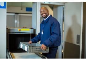 面带微笑的机场安检人员拿着传送带附近的板_10748129