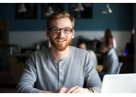 面带微笑的红发男子拿着笔记本电脑在咖啡馆_3955479