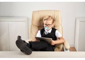 高加索男孩坐在办公室的办公椅上嘴里叼着_5839197