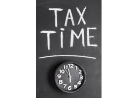 黑色表面带有纳税时间文字的闹钟提升视图_3991080