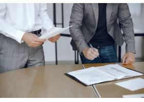 坐在律师办公桌前的生意人签署重要文件的_10701153