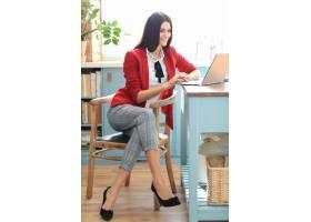 时尚的年轻黑发女子在家里拿着笔记本电脑工_11014369