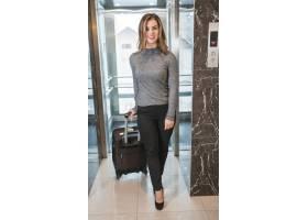 时髦的微笑着的年轻女子提着手提箱走出电梯_3716675