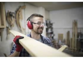 木工作坊提着木板护眼护耳的中年金发木匠肖_11137074