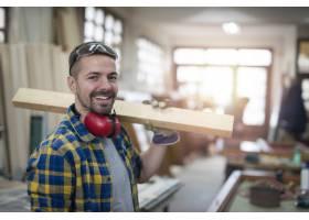 木工作坊里站着木板和工具的专业中年木匠画_11137101
