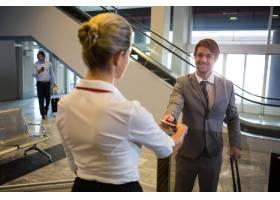 女工作人员在值机柜台检查旅客登机牌_8236054