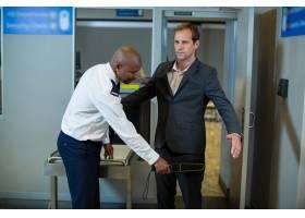 机场安检人员使用手持金属探测器检查通勤者_10748165