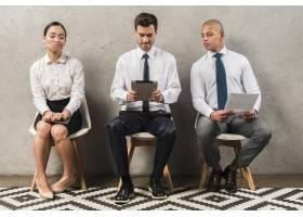 嫉妒的女商人坐在使用数字平板电脑的商人旁_4172197