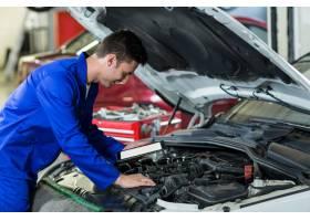 机械师在维修汽车发动机时使用数字平板电脑_1005037