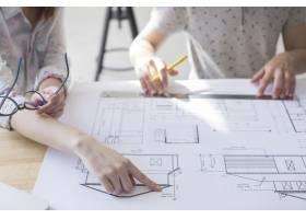 工作场所女性手指向桌子上方蓝图的特写_5061022