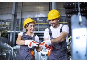 工厂工人在工业金属生产线上一起工作_11035670