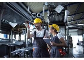 工厂工人在装满金属零件的工业仓库里用平板_11035569