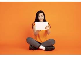 橙色工作室背景下的高加索年轻女子肖像_13455994