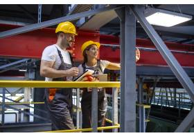 工厂的防护设备工程师们站在生产大厅里交流_11035694
