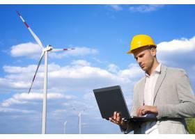 工程师在风力发电机前用笔记本电脑工作_11139372