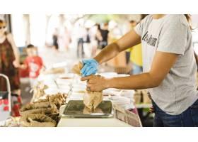 市场上的女小贩为她的顾客包装食物_5028428