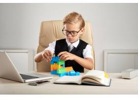 年轻的金发高加索男孩坐在办公室的行政椅上_5839199