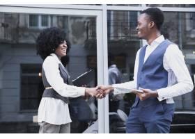 年轻的非洲商人和商人在玻璃窗前握手_4765017