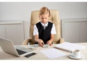 年轻的高加索男孩坐在办公室的行政椅子上_5839208