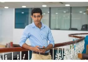 满足自信的年轻人在现代办公室里靠在栏杆上_3629188