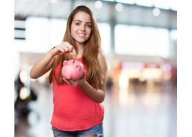 年轻可爱的女人用存钱罐存钱_998309