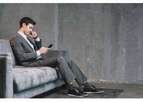 年轻商人坐在灰色沙发上用手机_3453288
