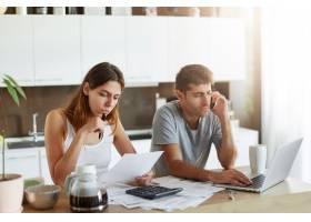年轻夫妇写真女性专心阅读文件男性坐在_9438540