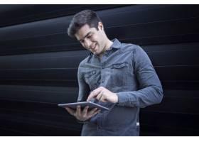 年轻帅哥在平板电脑上打字_11036554