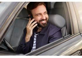 年轻快乐有魅力成功的大胡子男人坐在_10760172
