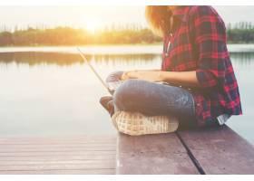 年轻快乐的时髦女人坐在馅饼上用笔记本电脑_1025805