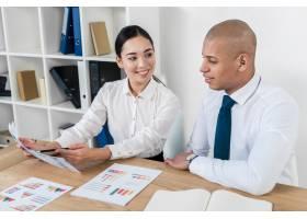 年轻的亚洲女商人向她的同事展示商业报告_4157582