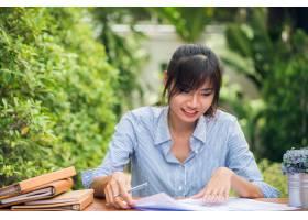 年轻的亚裔女性在户外的书桌上写作业女性_1375242