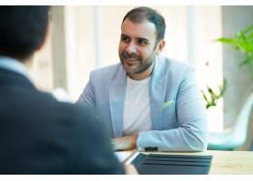 微笑的中年商人坐在办公室的肖像_3584971