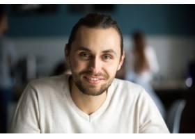 微笑的千禧一代男子在咖啡馆看着相机头像_3955480
