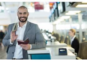 微笑的商人拿着护照和登机牌站在值机柜台的_10747914