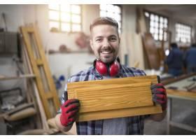 微笑的工匠在他的木工车间里拿着一件家具的_11137058