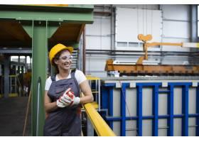 微笑的工厂女工站在工业生产大厅的肖像_11030673